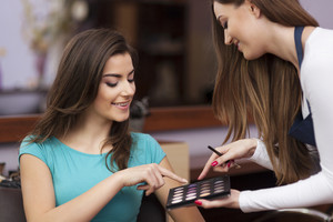 Woman with makeup artist choosing color of eyeshadow
