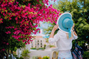 Woman with straw hat and vivid flowers. Amazing summer time on mediterranean sea. Romantic Traveling vacation concept