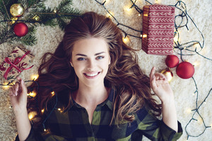 Woman wrapped in christmas lights lying on floor