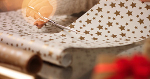 Woman's hands close up cutting white and golden wrapping paper for Christmas presents