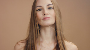 woman's portrait in studio in beige tones. blonde woman with long straight hair