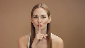 woman's portrait makes shhhh with a finger. Quiet please concept