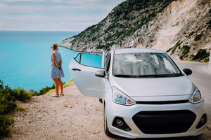 Women near rented car with open door enjoying Myrtos Beach. Travel vocation concept. Kefalonia, Ionian Sea, Greece