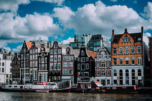 Wonderful architecture of Amsterdam. White fluffy clouds over Leaning Houses Amsterdam, Netherlands