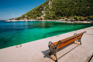 Wooden bench in front of the sea. Ecovillage at Ithaca island in Greece. Picturesque mediterranean town