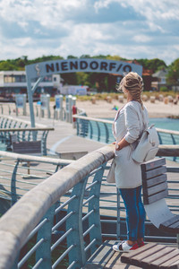 Woomen on pier near beach with roofed wicker chairs in Travemuende at the Baltic Sea. Travepromenade in Travemunde, a borough of Lubeck, Germany