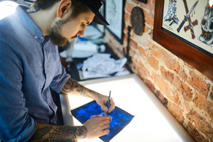 Worker of tattoo-salon drawing picture of adornment