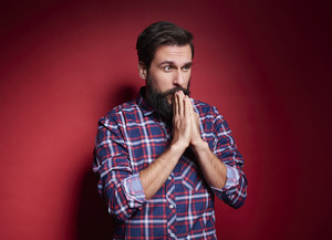Worried man praying at studio shot