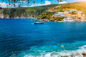Yacht arrived in beautiful Assos village located on Kefalonia with clear blue sea water on summer vacation trip around Greece