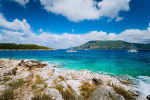 Yachts drift in middle of open crystal clear emerald green sea water near Fiskardo town. Ithaki Island in background. Amazing white cloudscape moving in blue sky, Kefalonia, Ionian islands, Greece