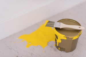 Yellow paint tin can with brush on top with yellow strokes on the wooden floor