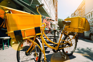 Yellow post bicycle made stop near building for delivery. Hamburg, Germany