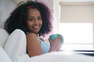 Young African American woman enjoying a cup of coffee in bed at home during weekend. Portrait of happy black girl smiling and sipping tea from mug.