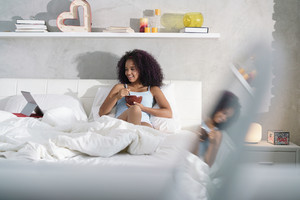 Young African American woman having breakfast in bed at home. Portrait of happy black girl smiling while watching movie on computer TV on weekend.