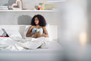 Young African American woman in bed at home during weekend. Happy black girl smiling while watching movie on laptop computer and drinking coffee