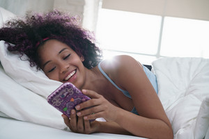 Young African American woman in bed at home. Happy black girl smiling while texting message on mobile telephone. Latina teenager lying in bed and using cell phone for social media and internet. Slow