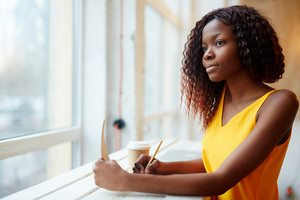 Young African girl making notes or drawing in her notepad