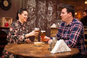 Young and cheerful couple drinking beer and having a good time Hipster pub.