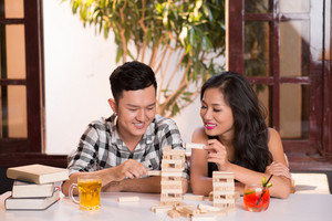 Young  Asian couple playing jenga indoors