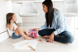 Young asian woman and her little daughter drawing together on a floor at home