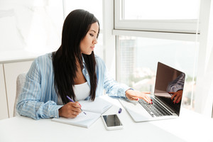 Young asian woman working with laptop and taking notes while sitting at the table indoors