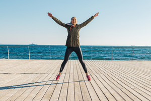 Young athletic woman jumping on the beach and doing sports exercises