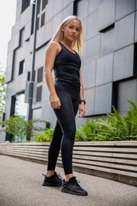 Young Athletic Woman Standing Against Building In City