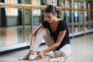Young ballerina with pointes sitting on the floor