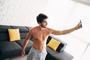 Young bare chested man training and working out at home. Handsome hispanic male athlete after a routine of exercise, taking a selfie picture or video with mobile phone for his blog.