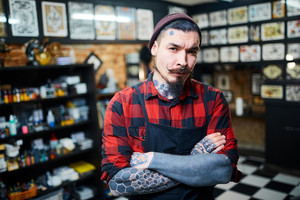 Young bearded hipster with tattooes on arms and face looking at camera