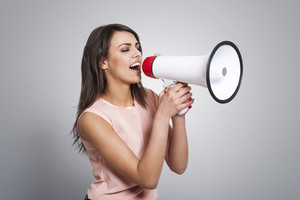 Young beautiful woman screaming by megaphone