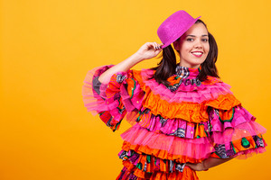 Young beautiful woman wearing a mascarade latino costume over yellow background in studio