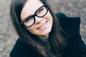 Young beautiful woman with glasses looks at the camera and smiles