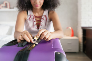 Young black woman packing and locking bag for holidays. Latino girl preparing padlock for travel suitcase. Close-up of hands and lock