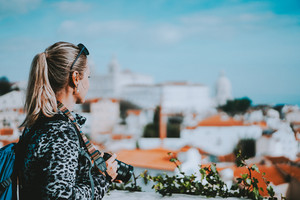 Young blonde woman admiring Lisbon cityscape. The National Pantheon and the towels of Vicente de Fora come into view. Red and white panorama of Lisbon