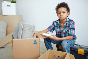 Young boy taking plate out of box with home supplies