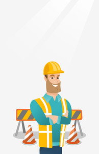 Young builder standing with arms crossed. Confident builder in hard hat. Caucasian builder in helmet standing on the background of road barriers. Vector flat design illustration. Vertical layout.