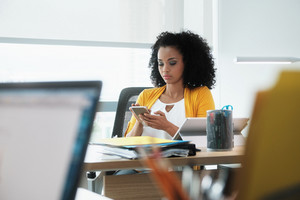 Young business woman working in modern office. Black businesswoman typing text message on mobile telephone. Busy African American employee using smartphone for email and internet at work
