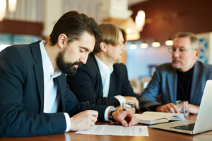 Young businessman signing contract after reading it