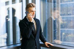 Young businessman with stylish haircut talking on phone while enjoying picturesque view from panoramic window of office lobby, waist-up portrait