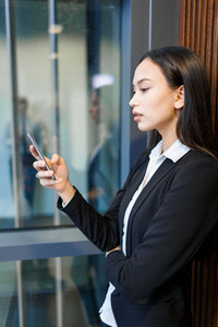 Young businesswoman reading sms in smartphone