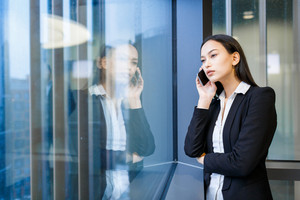 Young businesswoman talking on mobile phone by window