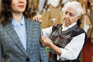 Young businesswoman trying on new jacket or suit in atelier