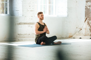 Young candid man sitting on a fitness mat and meditating in the gym