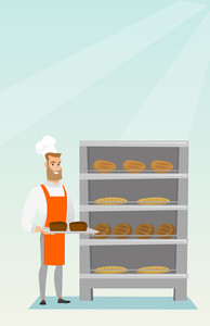 Young caucasian baker holding a tray with bread in a bakery. Confident male baker standing near the bread rack. Smiling baker holding a baking tray. Vector flat design illustration. Vertical layout.