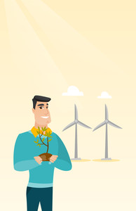 Young caucasian smiling worker of wind farm. Man holding in hands green small plant in soil on the background of wind turbines. Green energy concept. Vector flat design illustration. Vertical layout.