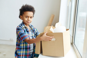 Young child holding open carton-box