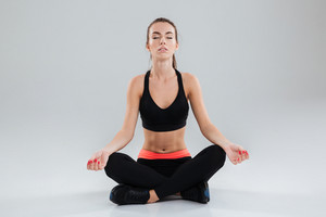 Young concentrated fitness woman sitting on the floor and doing yoga exercise with closed eyes over gray background