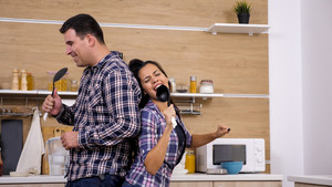 Young couple having a singing contest in their kitchen. Game on.