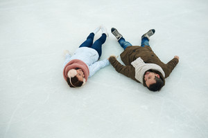 Young couple of skaters lying on ice